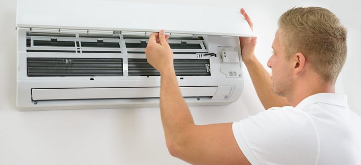 Five Things to Do When Your Air Conditioning System Breaks, Portrait Of A Young Man Adjusting Air Conditioning System