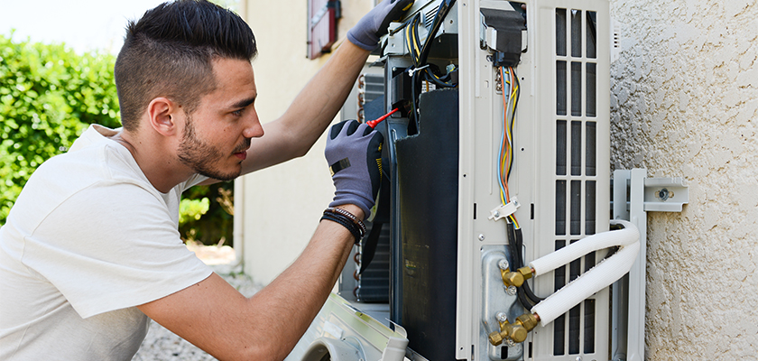 Image of a man troubleshooting AC Unit